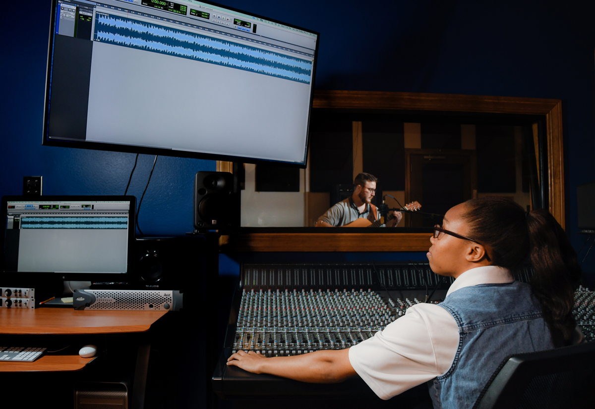 Will Flowers plays the guitar while Jalia Payne demonstrates how to record music with Louisiana Tech University's new ORIGIN analogue in-line console for hybrid production environments.