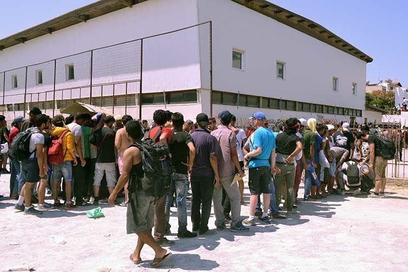 Migranten vormen wachtrijen aan het gemeentelijk stadion en wachten op registratie door de Griekse politie