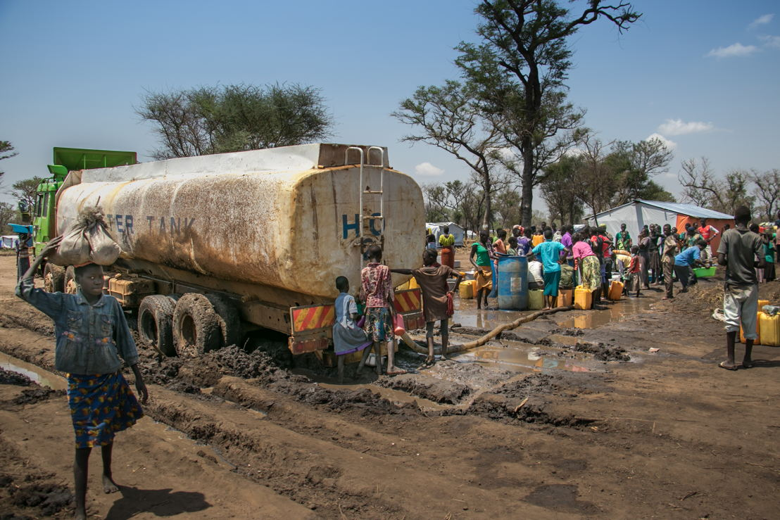 A water truck is stuck in the mud in Palorinya refugee camp, Uganda.<br/><br/>People take the opportunity to get much needed water when a water truck gets stuck in the mud after heavy rain. The impending rainy season will only make the situation worse as vehicles struggle to get around the camp. Photographer: Fabio Basone/MSF
