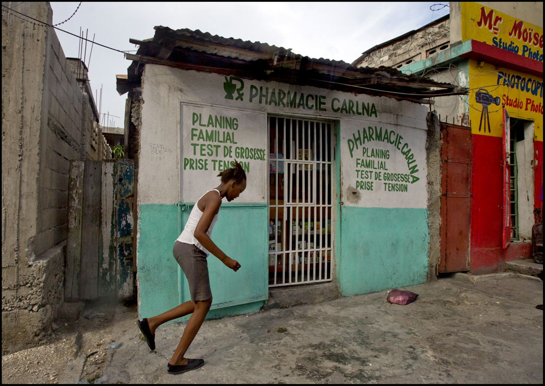 A young girl runs outside a typical pharmacy in downtown Port-au-Prince where misoprostol—a drug used to induce abortions—is readily available without prescription. In these cases, there is no control on the drugs and girls and women are not given instructions from a medical professional on how much to take or what to expect. They also receive no follow-up care. Misoprostol is used by medical professionals, including MSF, to administer a medical abortion (in combination with another drug—mifepristone), to induce labor, and to treat postpartum hemorrhage. Photographer: Patrick Farrell