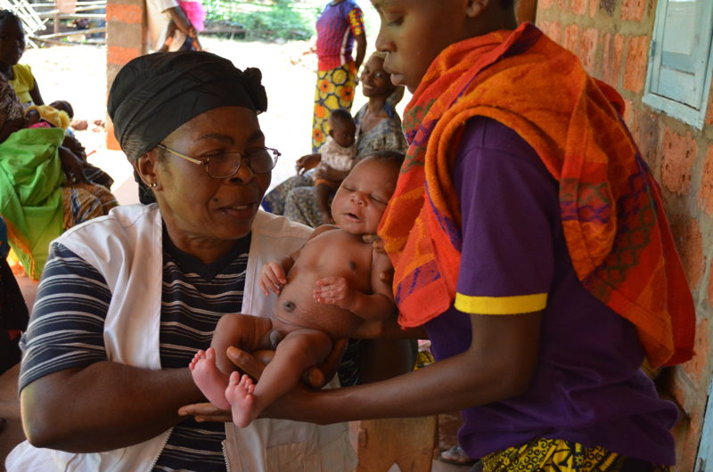A midwife in Mbalazime health centre weighs a newborn baby during a post-natal checkup. Mbalazime is one of three health centres supported by the MSF team in Bangassou, Mbomou prefecture, CAR. Between January and June 2016, 296 women gave birth safely in these three structures. Photographer: Sandra Smiley/MSF