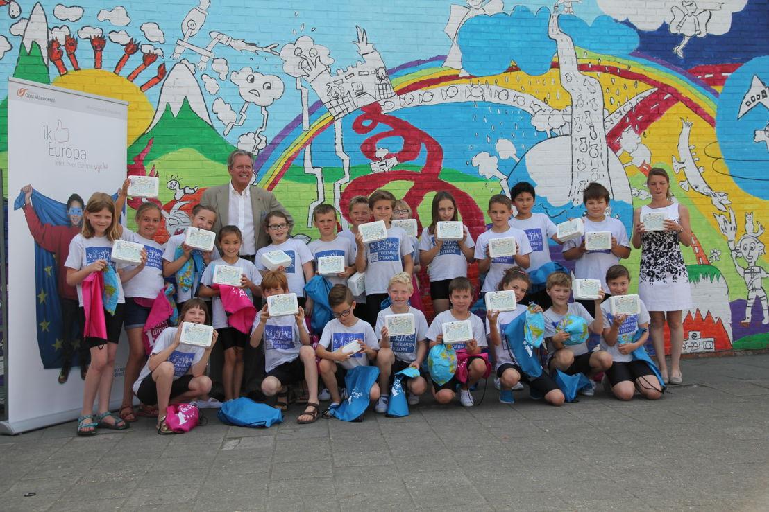 Gedeputeerde Geert Versnick en winnaar Elfien samen op de foto met de klas
