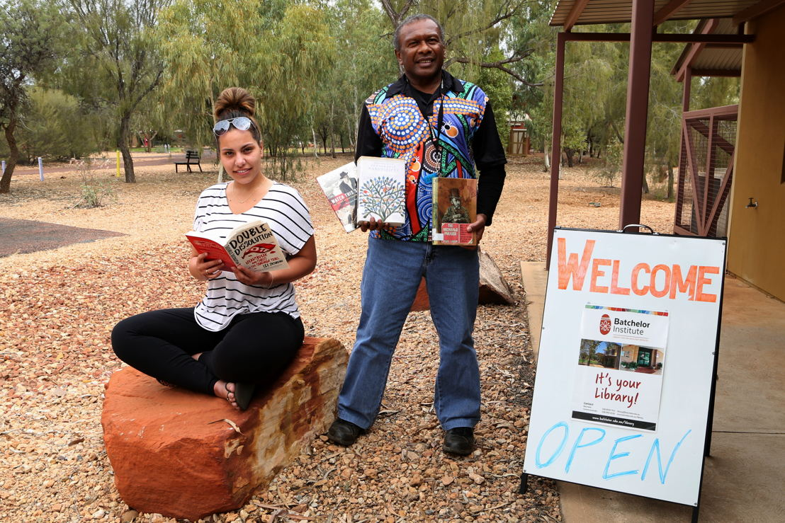 Batchelor Institute students Tiarne de Beer and Allen Minniecon in Alice Springs, with books donated by the ABC. Photo: Angela Harrison