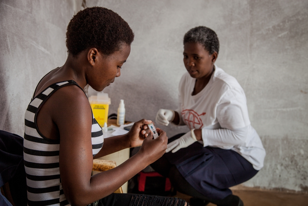 Community Health Agent Babongile Luhlongwane conducts an HIV test on Andile (28), who lives in the remote Entumeni District of KwaZulu-Natal, where HIV prevalence in South Africa is among the highest. If he tests positive, she will refer him to the nearest local clinic to be initiated onto ARVs. Babongile is one of nearly 90 dedicated health workers who are taking HIV counselling and testing to the most remote parts of KwaZulu-Natal. She says she enjoys teaching people how HIV works, and helping them to start on treatment if necessary. Photographer: Greg Lomas / Médecins Sans Frontières
