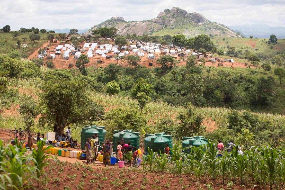 People queue outside a water storage and pump facility built by Medecins Sans Frontiers (MSF). The satellite camp of Kapise 2, less overcrowded than the main one, is in the background. The rock in the background is already beyond border between Mozambique and Malawi. <br/><br/>Over 5.800 Mozambican nationals have camped in the village of Kapise 2 in Malawi after fleeing their homes in Mozambique. The only regular water source in the village has ran dry and the only way to get water is from few pre-existing sources and the two additional boreholes respectively rehabilitated and constructed by MSF. Even then, waiting time is at times up to 2.5 hours at the water pump and with the continuous influx of people, the capacity of the borehole today can only provide around 8 liters of water per person per day, well below the minimum humanitarian standards of 15-20L. © James Oatway / MSF