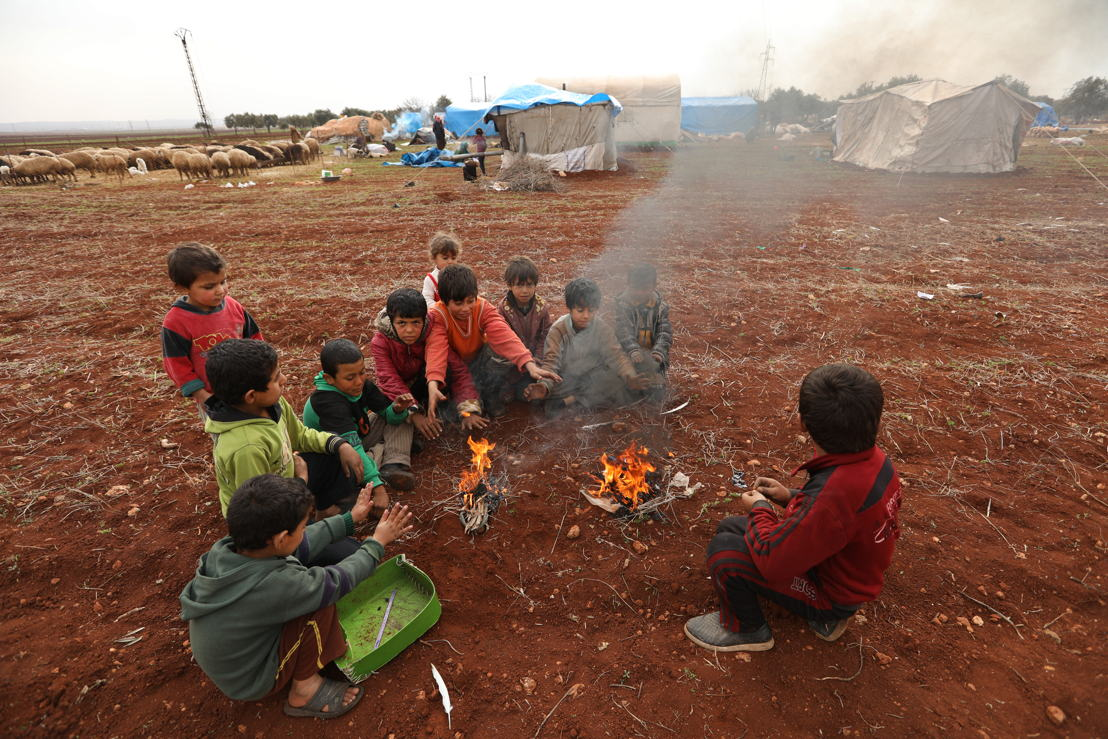 More than 212,000 Syrians have fled their homes due to an intensification of airstikes in northwest Syria. Most have very little or nothing to sustain themselves as winter sets in. Here, a group of Syrian children huddle near a fire to find warmth.<br/>Taken 12.1.2018, credit Omar Haj Kadour/MSF