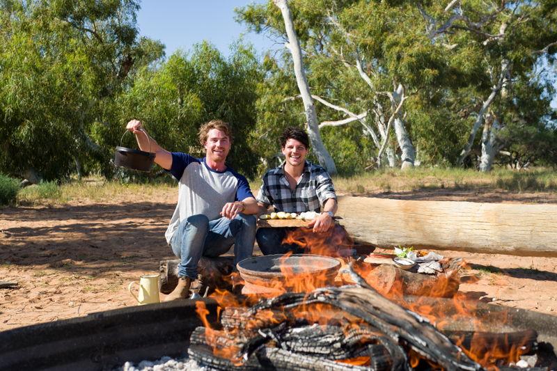 Hayden and Dan cook on the open fire
