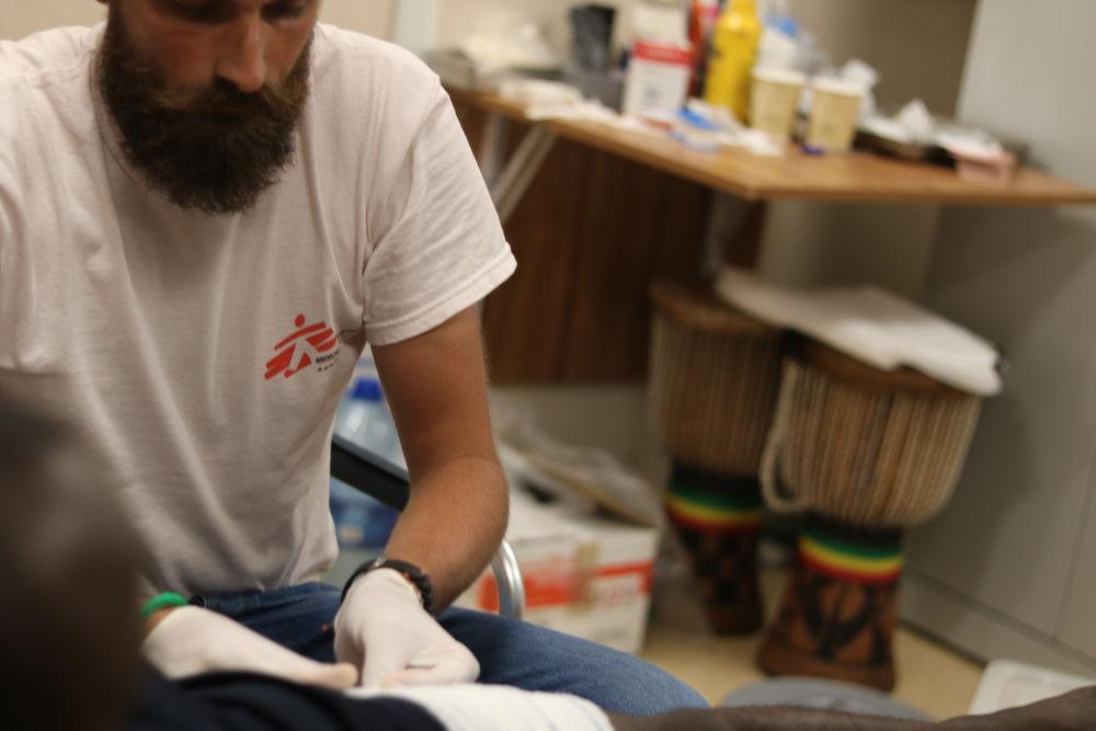 Luca Pigozzi realiza una cura a una personas rescatada que presenta una infección en una pierna causada por la exposición a condiciones de vida insalubres durante un período prolongado de tiempo. © Hannah Wallace Bowman/ MSF