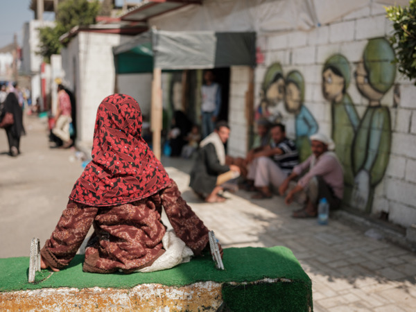 A girl sits on an anti-vehicle concrete barrier built in front of the mother and child hospital run by MSF, while men sit outside the entrance of the cholera treatment unit. Taiz Houban, Yemen, March 2018. Credit  Matteo Bastianelli