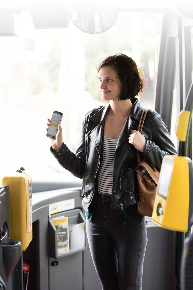 Een vrouwelijke reiziger toont haar digitaal ticket aan de chauffeur.