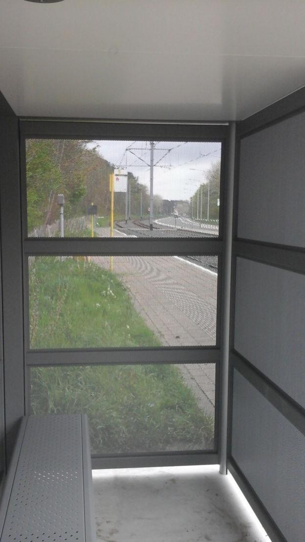 De stalen wanden van het vandalismebestendig schuilhuisje zijn doorzichtig dankzij perforaties van 4 cm. (Foto: De Lijn)