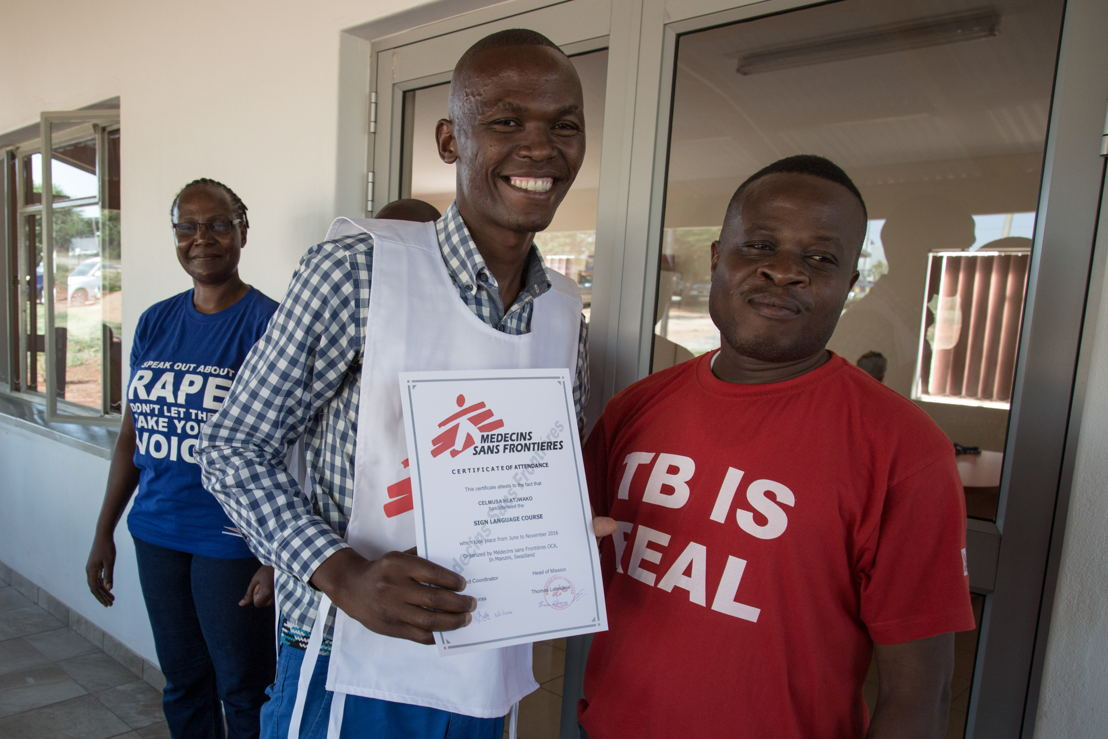 Celumusa Hlatswako (center), MSF mobile counselor, receives a sign language qualification certificate. He wanted to learn sign language to be able to communicate and help deaf MDR-TB patients. Hearing loss is one of the side effects of the MDR-TB treatment. Behind him, in the blue shirt, is Sellah Moraa, the MSF project coordinator of Matsapha clinic. Next to him, red shirt, Dr. Emmanuel Masombuko, MSF Medical Team Leader. Matsapha, Manzini Region, Swaziland. Photographer: Alexis Huguet