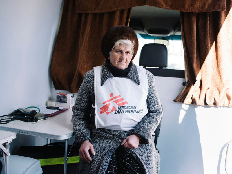 A volunteer MSF health worker sits in the back of a mobile medical clinic, run from a van, that serves the population of Mayorsk, Ukraine, near the frontline between government and opposition forces. Photographer: Christopher Nunn/MSF