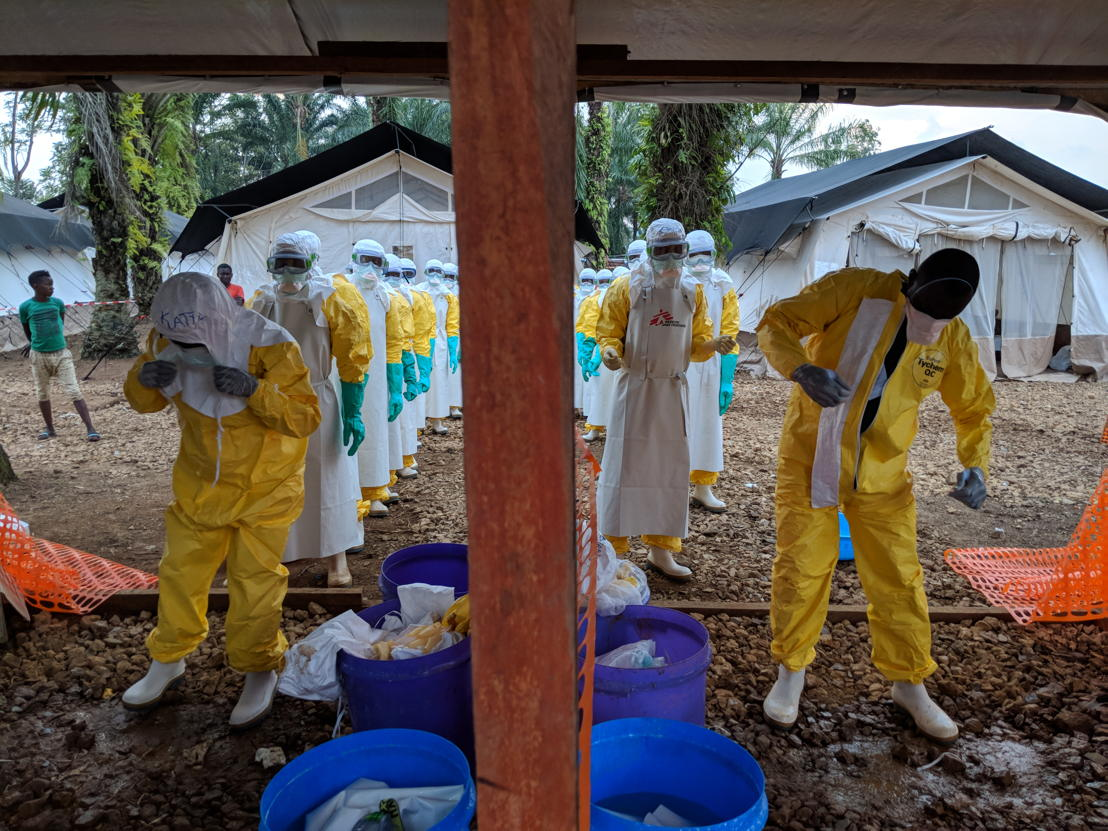 A team that has just finished setting up a tent in the high-risk zone in the Ebola treatment centre, getting out of their personal protective equipment (PPE). It's hard work, and harder still in such attire. Photographer: Karin Huster/MSF