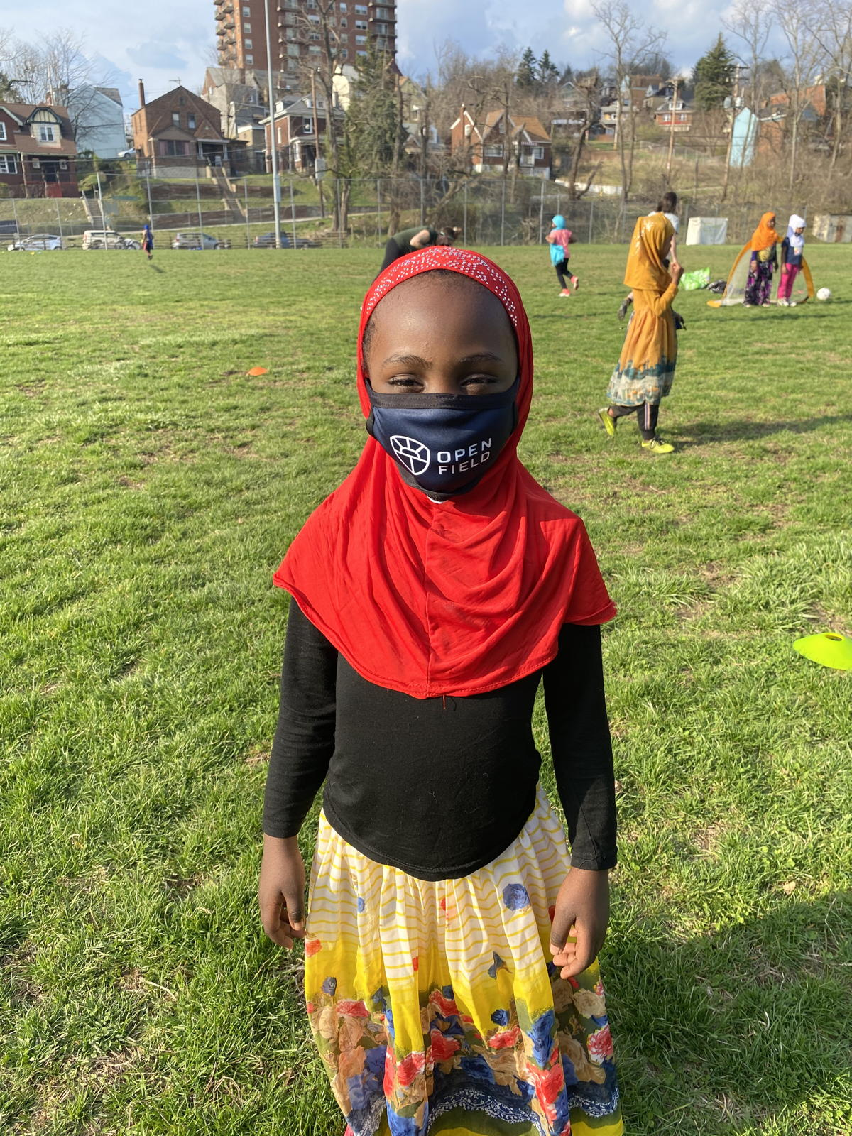 A youngster in a facial covering poses for a photo during one of Open Field