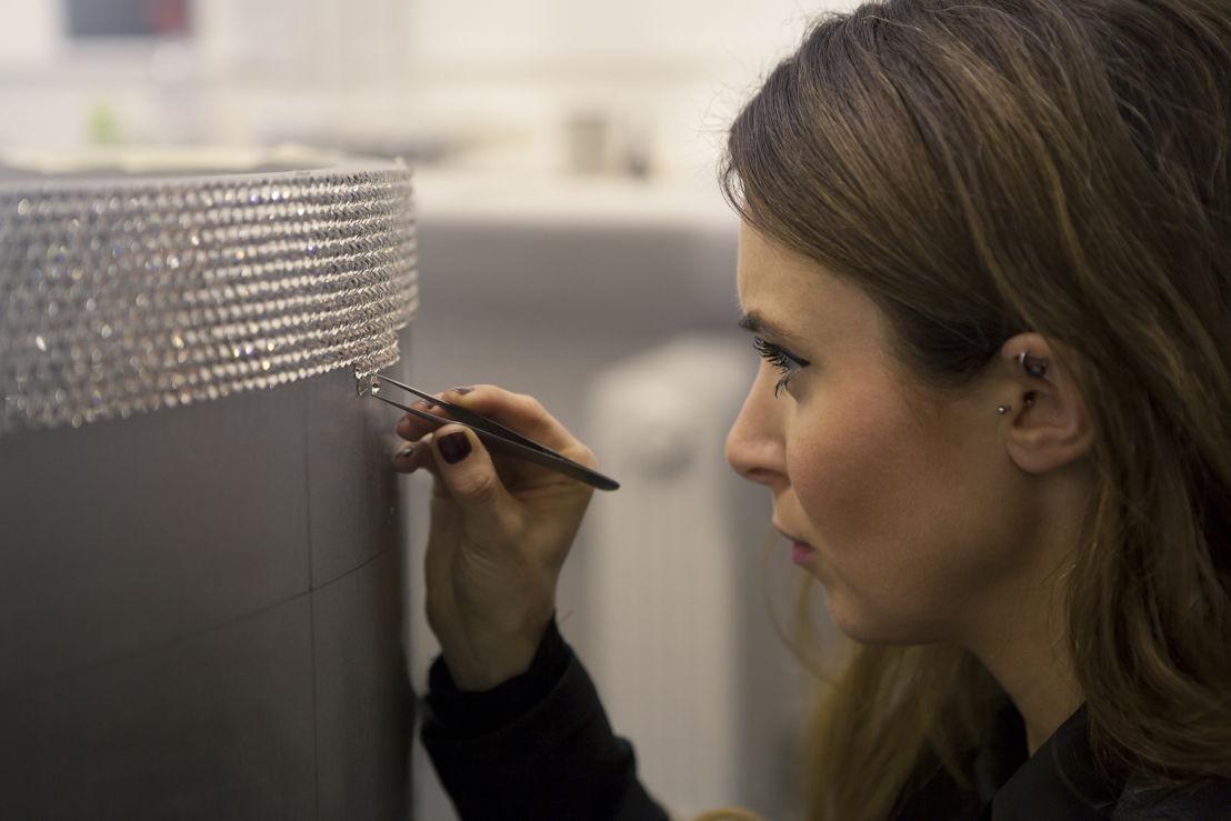 Artist Lauren Baker carefully applying half a million Swarovski crystals to the Goldfinch piano.