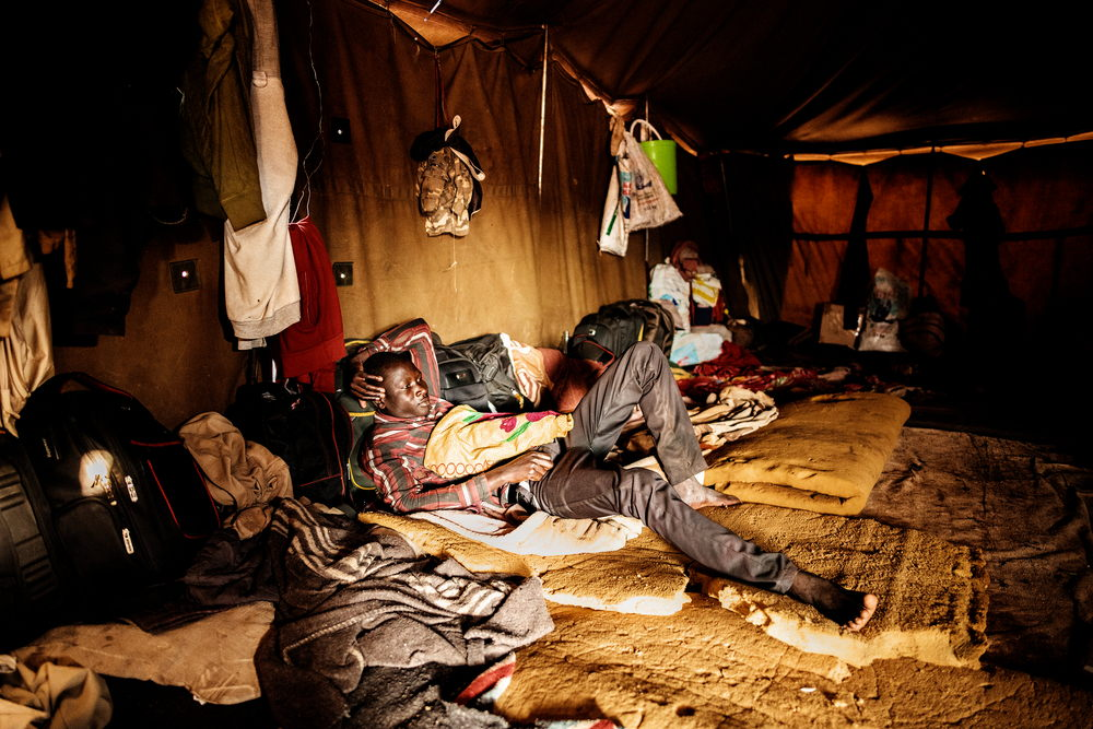 A migrant rests in a tent at a temporary shelter where migrants entering South Africa through Musina take refuge.  © Luca Sola 2019