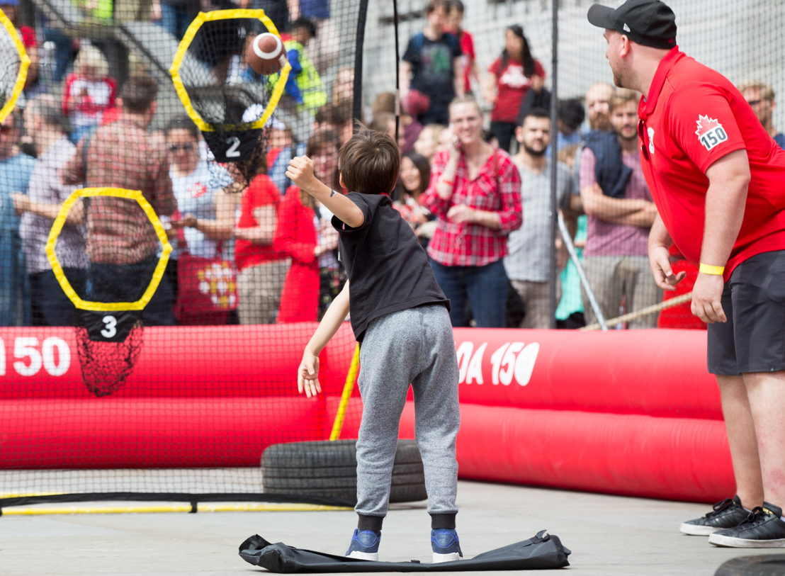 A young boy knocking out one of the targets in the obstacle course. Photo Credit: Jim Ross/CFL