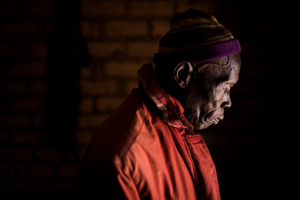 """Jean, 84, left Nasima on 6 Decembre 2016 with his family to find shelter at Aviation IDP camp. """"There was infighting between the UPC and FPRC near the village and there was a rumour that they were burning villages, so we fled. My son went back later to see what was left. All had been burned. I would like to go back to my village, but I have no money left to pay for transportation"""". Karim's son provides for his survival. Photographer: Colin Delfosse"""
