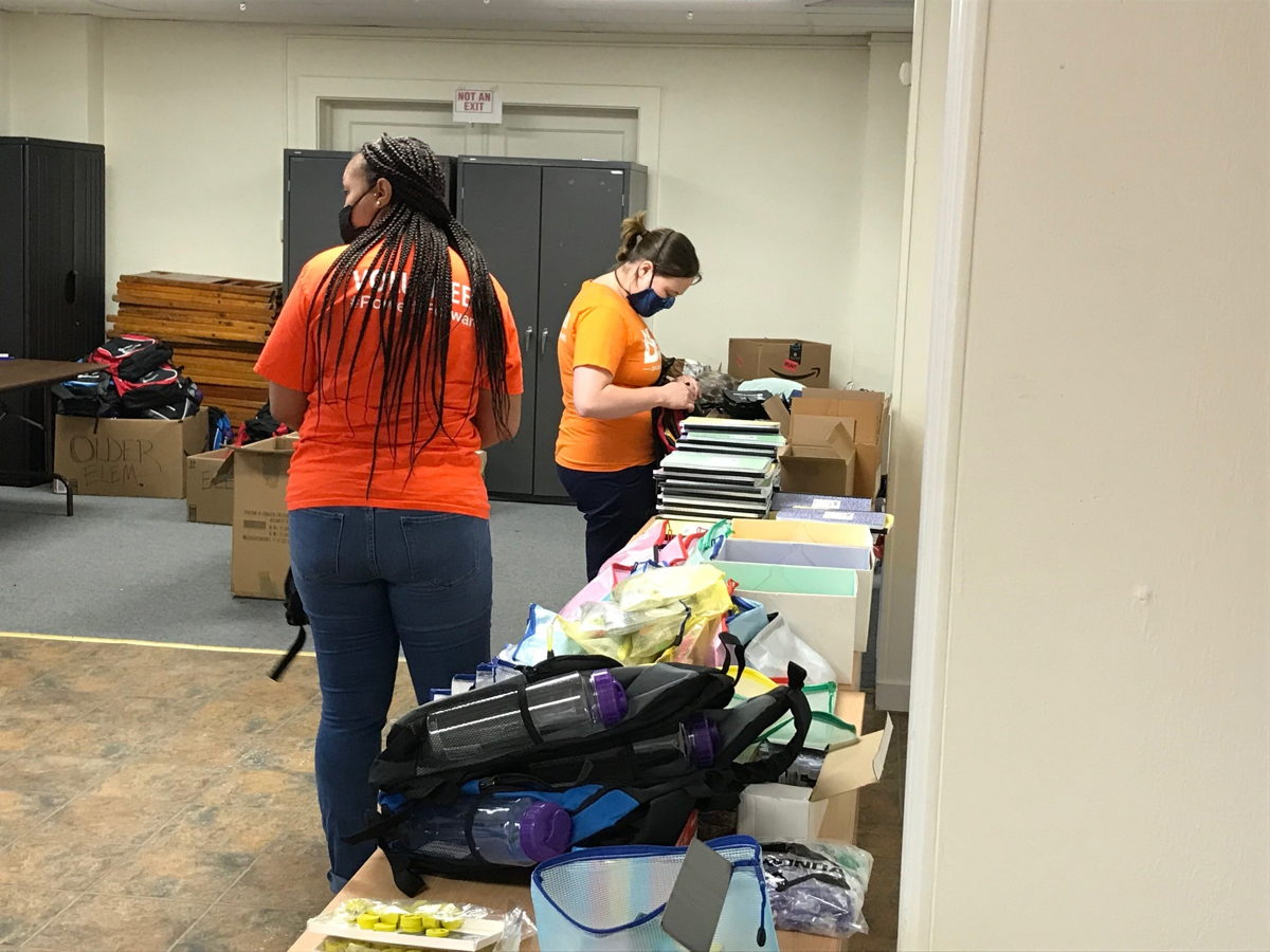 DLC volunteers Jenna DeLozier (right) and Amber Watson help fill backpacks with supplies for Hosanna House