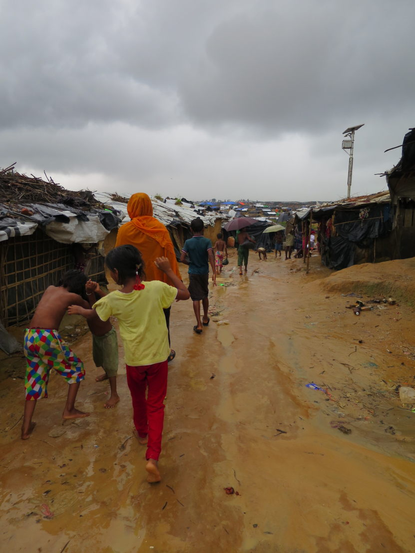 Children walk through the rain and mud at Kutupalung informal settlement in Cox's Bazar, Bangladesh. Photographer: Amelia Freelander