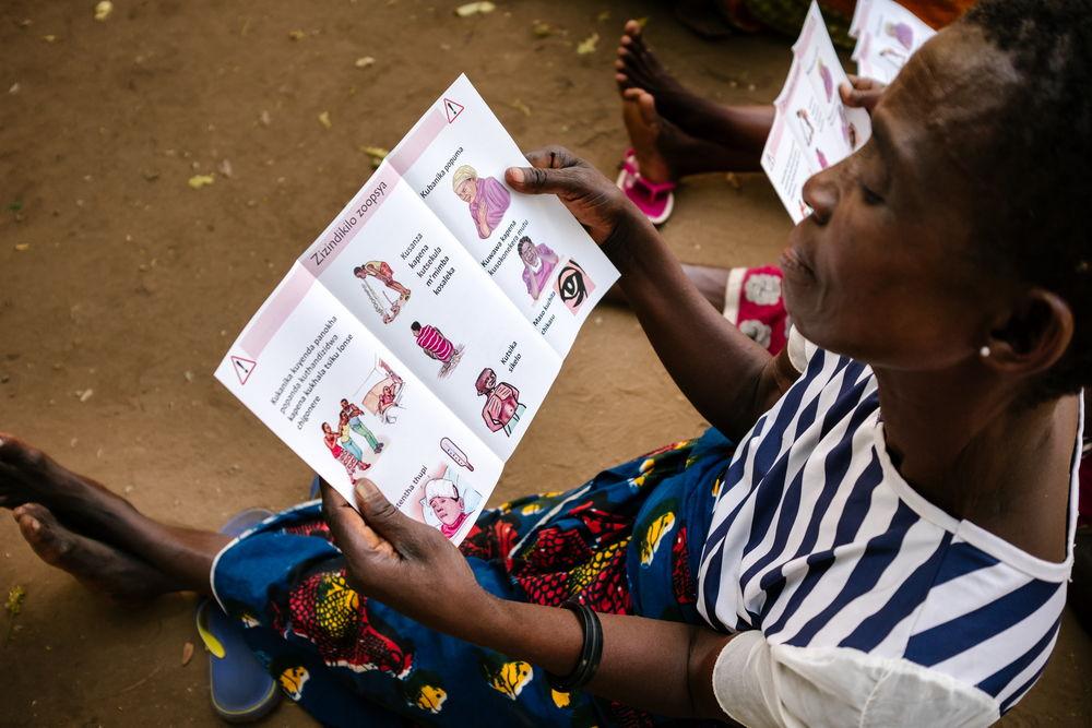 Una mujer lee un folleto con las señales de alerta para detectar el VIH. Isabel Corthier/MSF