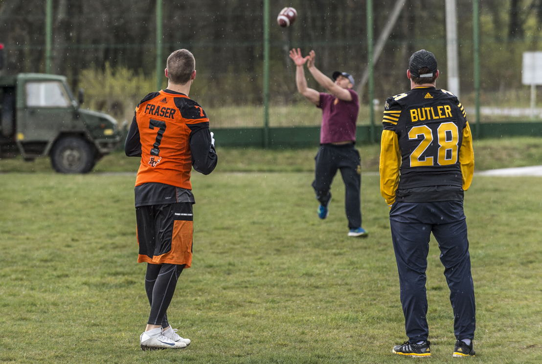 Eric Fraser (L) and Craig Butler (R) participating in a football drill with military members deployed on OP UNIFIER in Starychi, Ukraine. Photo: MCpl Mathieu Gaudreault, Canadian Forces Combat Camera