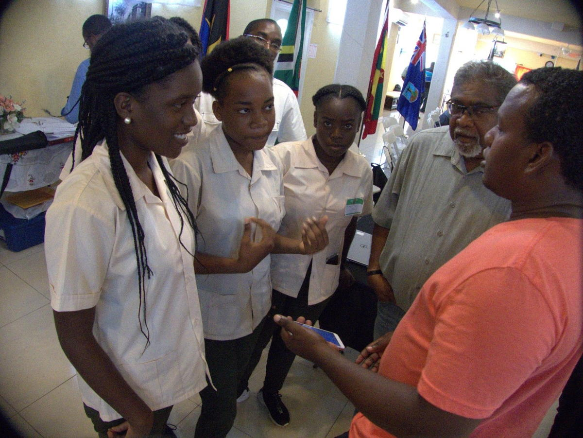 Farmer, Garvey Charlemagne, demonstrates ICTs on his mobile phone as a networking tool Sir Arthur Lewis Community College Students.