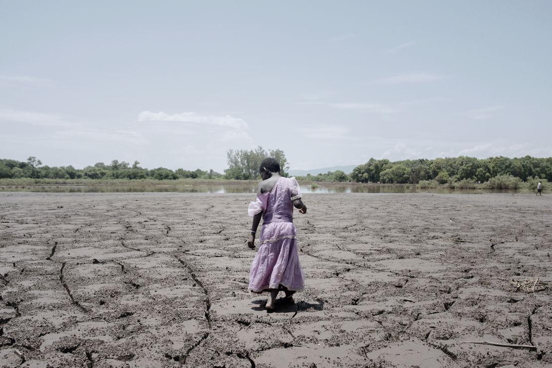 © Luca Sola<br/>Alesi Phiri, 7 ans, enjambe un vaste champ de boue séchée. Au début de l'année 2015, le Malawi a été victime d'énormes inondations. L'eau et la boue ont laissé derrière elles des champs détruits, une catastrophe pour une région où 85% de la population vit de l'agriculture.