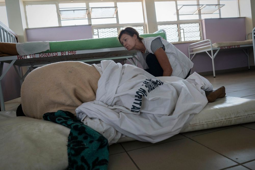 Linda Buijze, MSF nurse activity manager, a trained psychiatric nurse, checks a patient in the mental health hospital run by MSF. The patient lies on the ground so she can't fall out of the bed. Rachel Corner/De Beeldunie