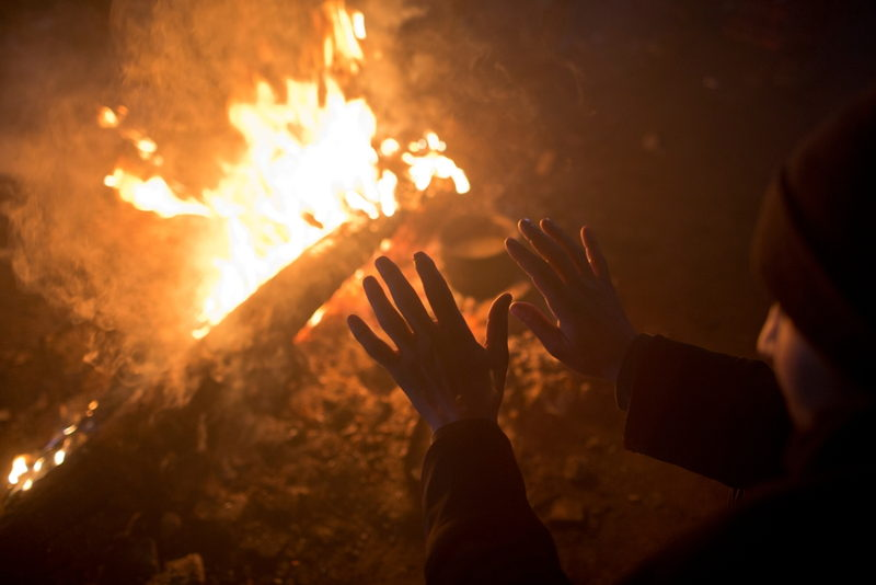 A man warms his hands by a fire inside an abandoned warehouse used by refugees as shelter in Belgrade, Serbia.  Photographer: Marko Drobnjakovic
