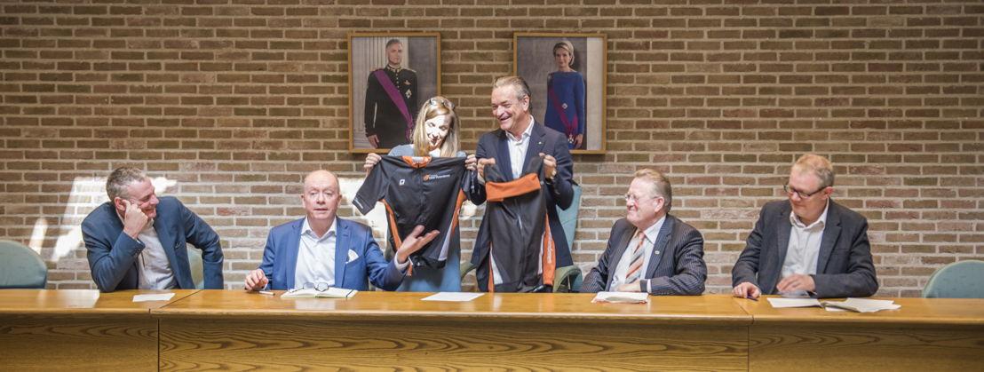 Gedeputeerde Hilde Bruggeman overhandigt een wieleroutfit aan de burgemeester van Herzele Johan Van Tittelboom