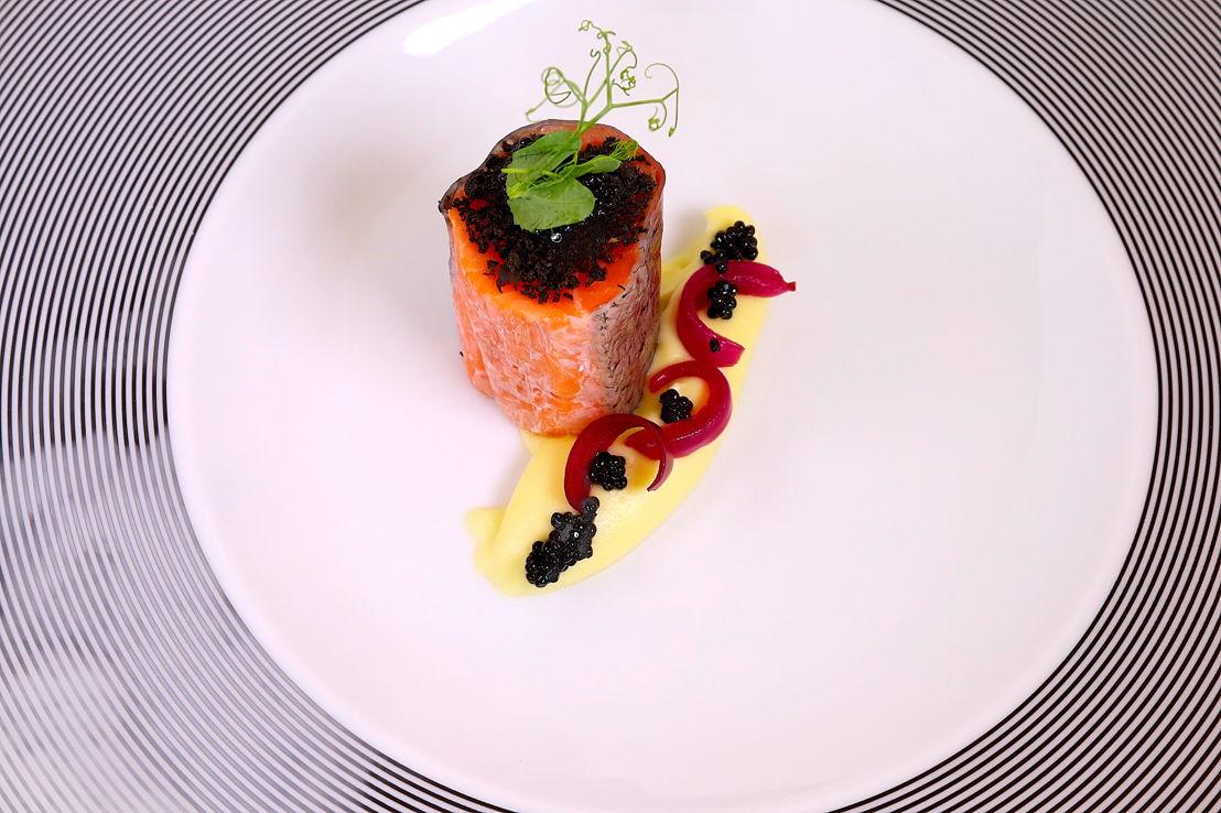 Filetto di trota affumicata su patate all'olio di oliva con cipolla rossa in scapece, pane nero e caviale
