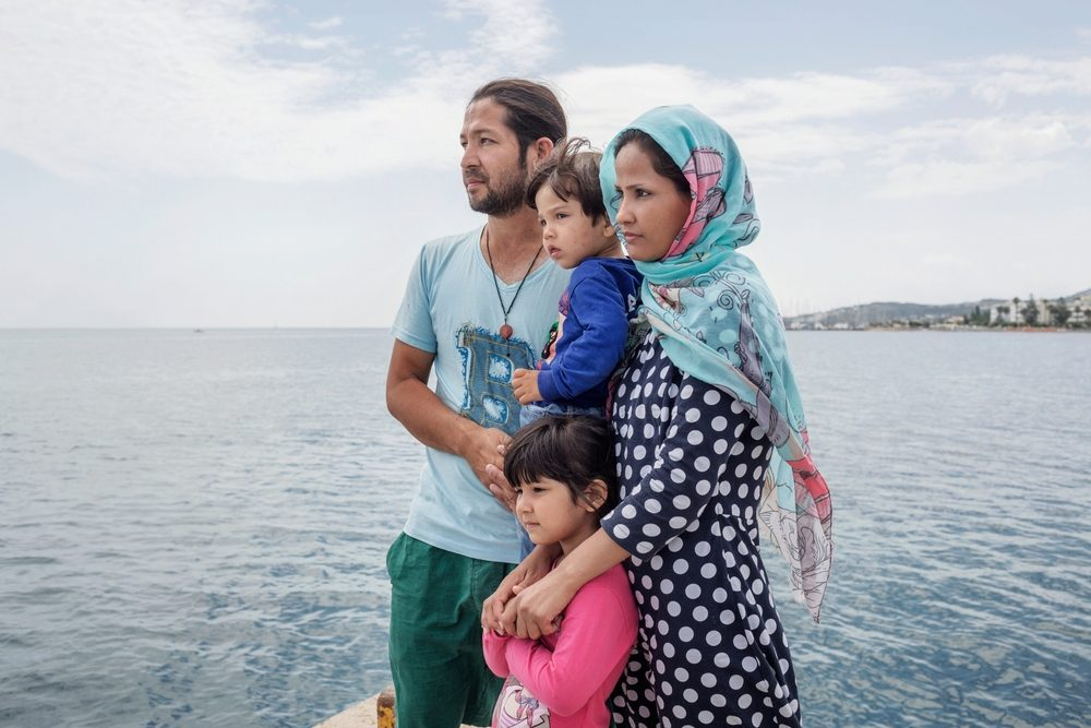 """System identifier<br/>: MSF148193<br/>Title<br/>: Migrants in Kos, Greece<br/>Photographer / cameraman<br/>: Alessandro Penso<br/>Countries:<br/>Greece 2015. Kos. Greece. An Afghan family at the pier on the island of Kos. Earlier, they were waiting in vain outside the nearby police station to get the necessary papers which would allow them to leave the island. """"I've come to Europe to give my children the best"""" says the father of the family. """"I don't know when I can get my papers."""". For seven days, the family was staying in the disused Captain Elias hotel, which the Kos authorities direct migrants to stay in while they await the authorization from the police to leave the island. However, they decided to move out because of the unhygienic conditions: """"It's dangerous for the children because there are a lot of insects.`My children have insect bites all over their bodies. When I was sleeping there was an insect that crawled into my ear and it's still there now."""""""