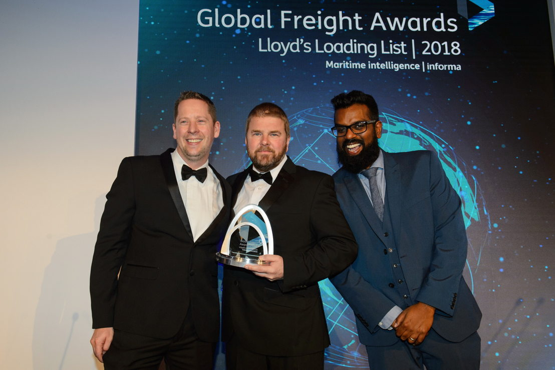 Ross Barnett, Emirates Cargo Manager, UK (centre) receives the award for Cargo Airline of the Year from Jonathan Stott, 2018 awards' judge & Import General Manager at Sainsbury's Argos (left) with Romesh Ranganathan (right), Master of Ceremonies for the Awards