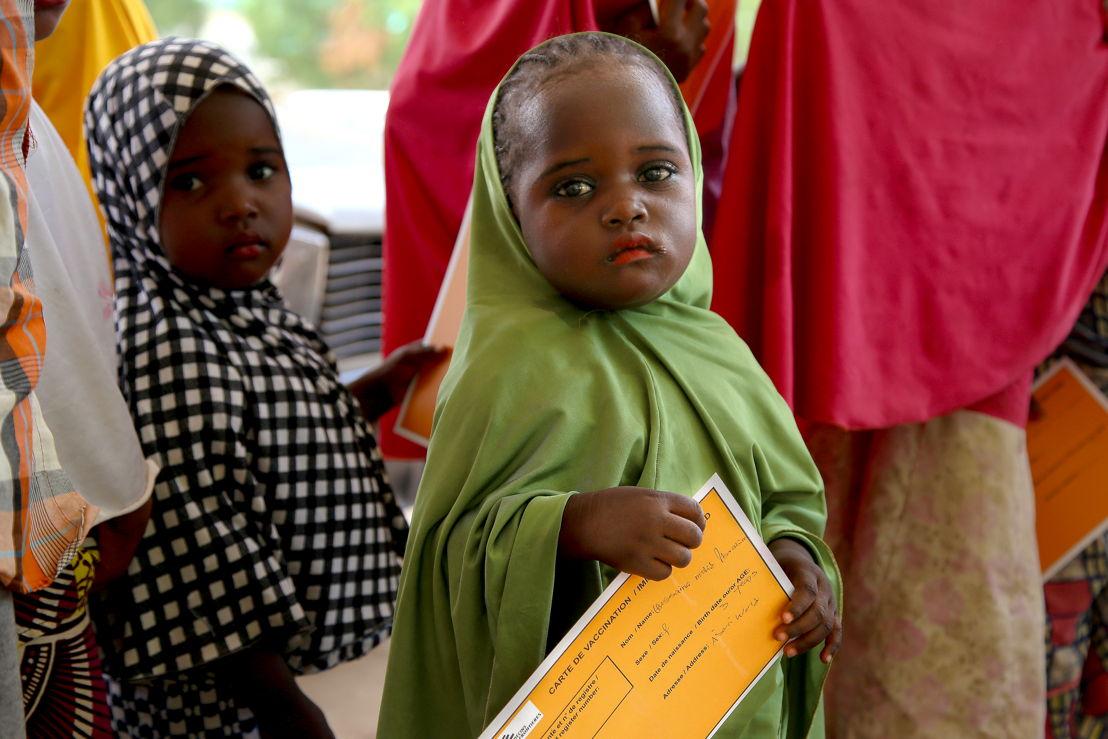 나이지리아 난민들을 위해 백신 캠페인을 실시하고 있다. 어린 소녀가 백신 카드를 손에 쥔 채 차례를 기다리고 있다. [Igor Barbero/MSF]