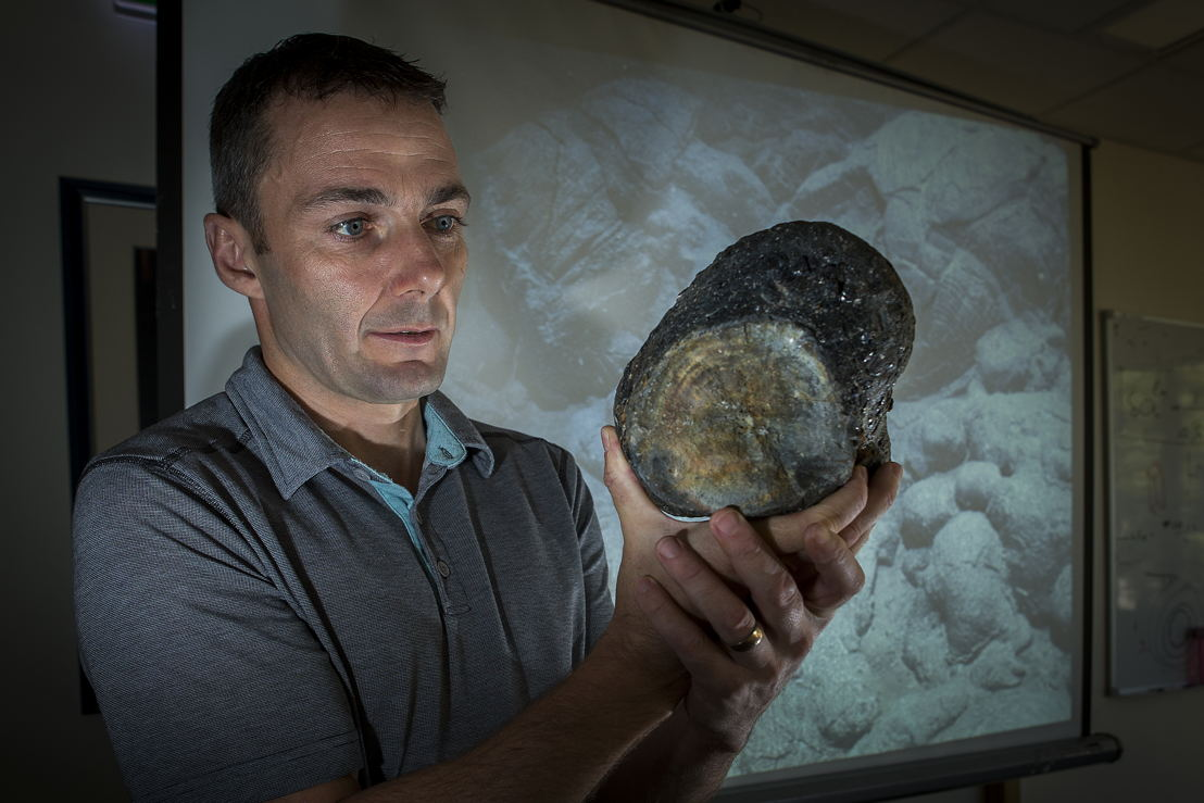Dr Mark Kendrick with a sample of volcanic glass. Image: Stuart Hay, ANU.