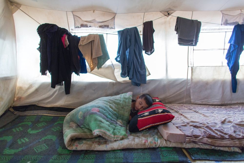 A young boy sleeps in his family's tent in Khanaqin refugee camp in northern Iraq. In the camp, MSF provides mental healthcare, treatment for non-communicable diseases and health promotion activities for people displaced by violence in neighbouring regions. Photographer: Ton Koene