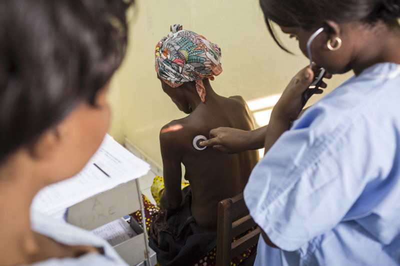 Kinshasa, Democratic Republic of Congo (DRC): An MSF doctor osculates a patient's lungs to check for abnormalities in MSF's HIV unit, which provides the only free hospital care for AIDS in the country. In DRC, HIV affects under 2% of the population and is highly stigmatized. People living with HIV also face frequent stock outs of drugs and high costs of tests and treatment. Photographer: Kris Pannecoucke