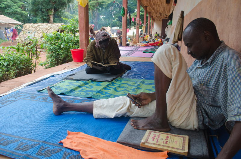 """Muslim men reading the Quran in the Saint Louis IDP site in Bangassou. Around 2000 Muslim people sought refuge on the Church site when the Muslim neighbourhood, Tokoyo, was attacked on May 13th 2017. They cannot leave it for fear of being killed by """"auto-defense"""" groups in town. Water is provided by the church and food is sparse, randomly distributed by humanitarian actors. MSF organizes daily mobile clinics on the site to provide primary health care. Photographer: Natacha Buhler"""