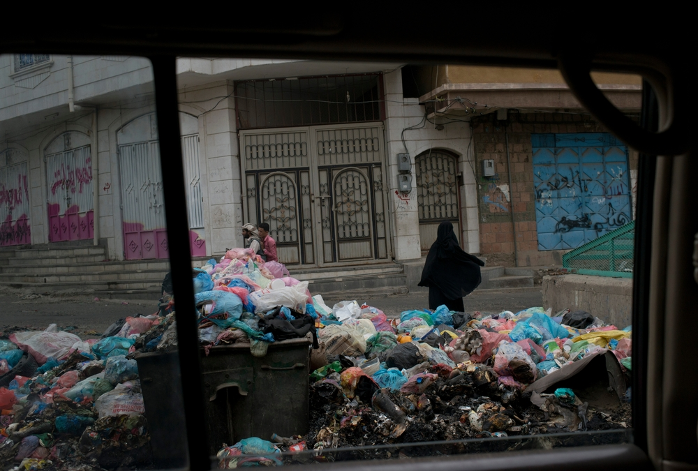 A Yemeni woman waks past garbage lining the streets on July 24, 2015 in<br/>Taiz, Yemen. Taiz has been the site of heavy<br/>fighting, and nearly all civil services have<br/>stopped.<br/>Credit: MSF