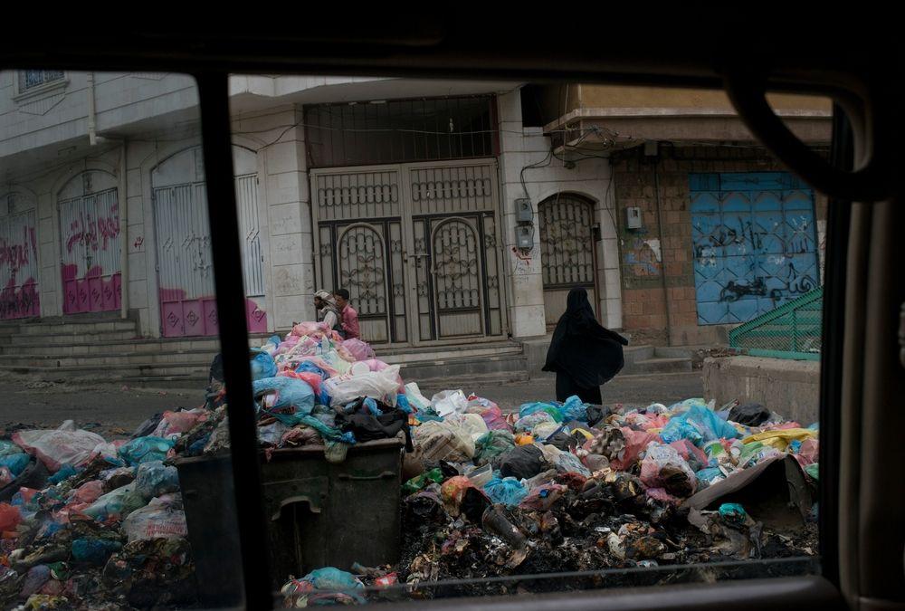 AYemeniwomanwakspast garbageliningthestreetsonJuly24,2015in<br/>Taiz,Yemen.Taizhasbeenthesiteofheavy<br/>fighting,andnearlyallcivilserviceshave<br/>stopped.<br/>Credit: MSF
