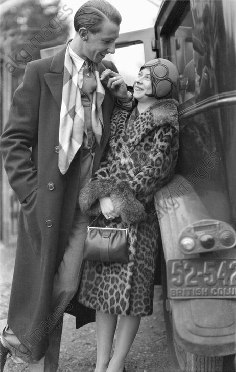Young fashionable couple standing by a car.<br/>Photo, 1927.<br/>AKG1046029