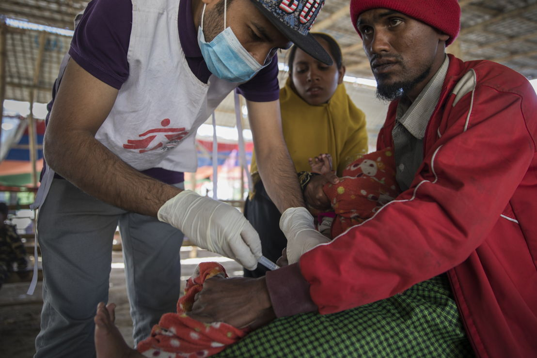 Boshir Ullah, a 25-year-old Rohingya refugee, has just arrived from Myanmar along with his wife, mother, and three children. In the photo, Ferungada, his youngest child, is being vaccinated by an MSF staff at Sabrang entry point. Photographer: Anna Surinyach