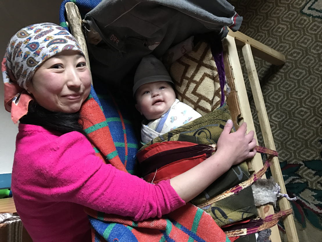 Kazakh mum and baby at home in yurt
