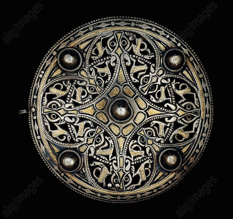 The Strickland Brooch.<br/><br/>(Central hollow-sided cruciform design with a boss at its centre and animal-head terminals).<br/>Sheet silver with inlaid gold and niello ornament,<br/>diameter 11.2cm. British Museum, London<br/>AKG644200