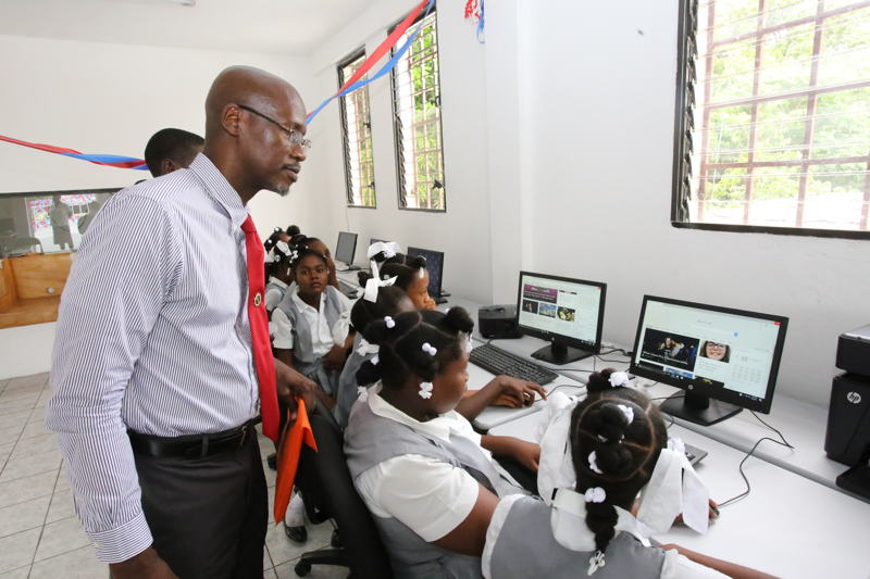 Students at the computer equipment donated by ECTEL, Managing Director Embert Charles looks on.