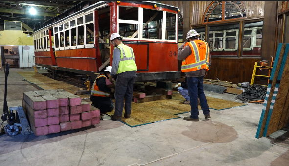 Crews prep streetcar #54 for its move across the new Urban Putt Denver space where it will be used for private parties and dining space.