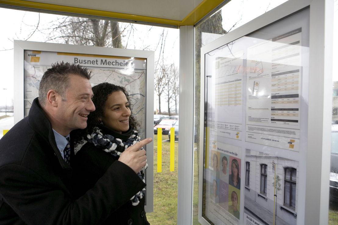 Reizigers raadplegen een dienstregeling in een schuilhuisje van De Lijn<br/>Foto: Stefaan Van Hul