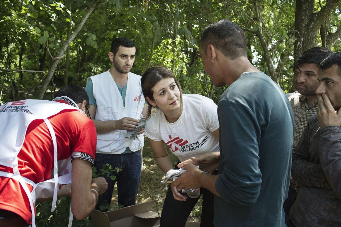 Idomeni. Grèce. La psychologue de MSF Aggela Boletsi et son collègue traducteur Mohammed distribuent des articles de première nécessité à un groupe de migrants.